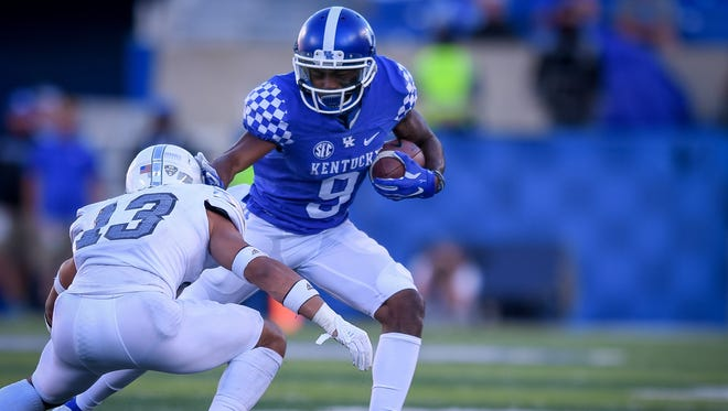 Kentucky Wildcats wide receiver Garrett Johnson (9) avoids the tackle of Eastern Michigan Eagles defensive back Justin Moody (13)during the game at Kroger Field on the campus of TheUniversity of Kentucky in Lexington, Ky, Saturday, September 30, 2017.