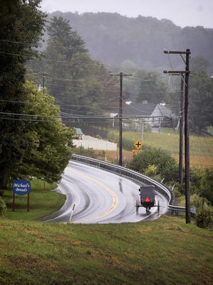 An Amish buggy travels down a long stretch of road in Lancaster County.