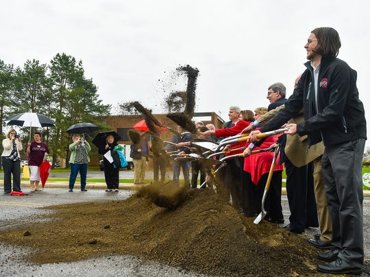 Soil is thrown from shovels as a part of the groundbreaking ceremony for  the new Science and Engineering Building at The Ohio State University at Marion on Thursday.