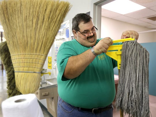 James Ramsey attaches the mop head to the pole as he cleans the men's room at the Vocational Rehabilitation Office  on Thursday. Ramsey is part of the supportive employment program at Journeys in Community Living.