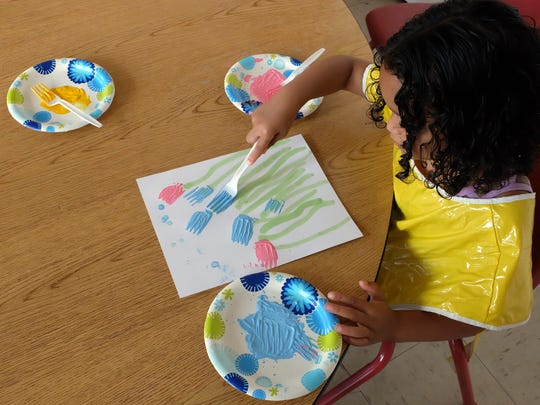 Edlise Perez, 4, paints flowers during the child care