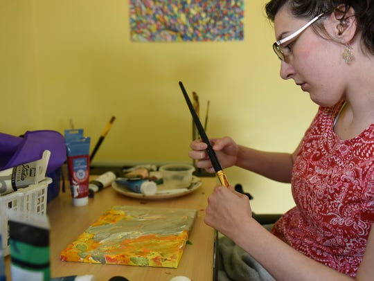 Beth Koenigsknecht, 31, pictured at her painting table