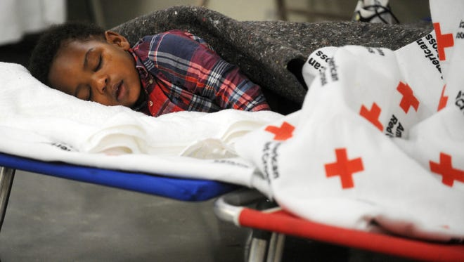 Prince Kirkland, 1, of Hattiesburg takes a nap at the Forrest County Storm Shelter, in Hattiesburg, Miss., Sunday, Jan. 22, 2017. Kirkland and his family were displaced after a deadly tornado swept through the Hub City in the early hours of Saturday morning. (Ryan Moore/WDAM-TV, via AP)