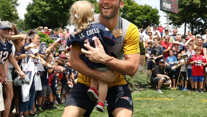 Patriots receiver Julian Edelman scoops up his young daughter, Lily Edelman, during training camp in 2018. According to a report, the Patriots won't be back at Gillette until training camp opens in late July.