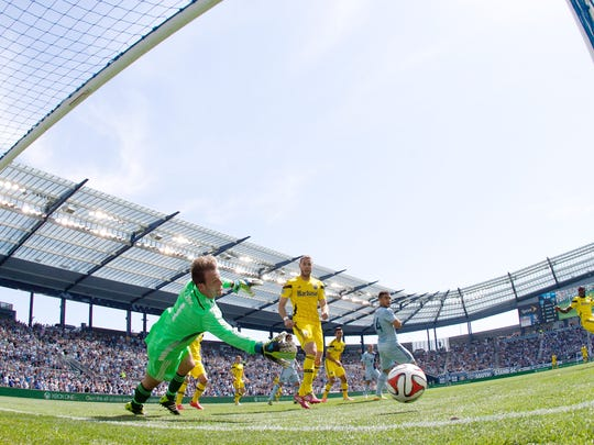 Columbus Crew goalkeeper and Mason native Steve Clark dives to stop a shot from Sporting KC' Jacob Peterson (from Portage, Mich.) during at 2014 match in Kansas City.  Clark, now in his third season with Columbus, has started 82 straight games for Crew SC.