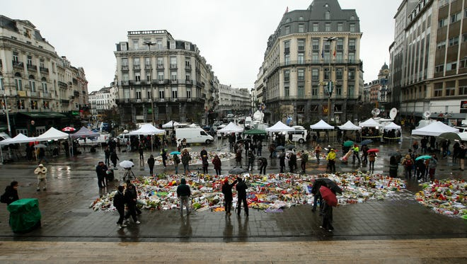 """A general view showing one of the memorial sites for the victims of the recent attacks in Brussels, and the media surrounding the area at the Place de la Bourse in Brussels, Friday, March, 25, 2016. Amid signs that life in Brussels was returning to some sort of normality on the third day of mourning the dead, authorities lowered Belgium's terror-threat level by one notch. However, they said the situation remained grave and another attack is """"likely and possible."""" Belgium had been on its highest alert since Tuesday's bombings. (AP Photo/Alastair Grant)"""