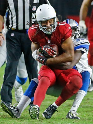 Arizona Cardinals wide receiver Larry Fitzgerald became the second-youngest player to reach 12,000 career receiving yards on this catch against the Detroit Lions in their game on Sunday, Nov. 16, 2014, in Glendale.