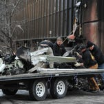 Workers load the remains of a small plane that crashed into two office building in downtown Anchorage, Alaska, on Dec. 29, 2015.