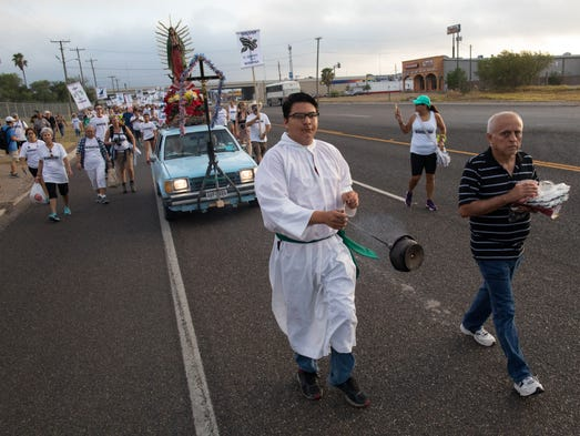 Altar server Anthony Saenz leads a march to La Lomita