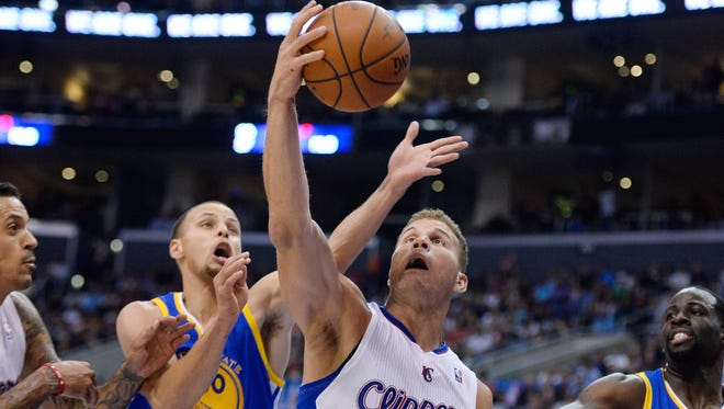 Los Angeles Clippers forward Blake Griffin (32) grabs a rebound away from Golden State Warriors guard Stephen Curry (30) during 4th quarter action in game five.