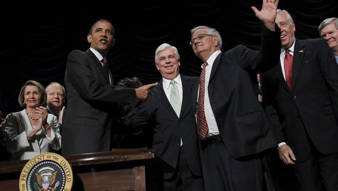 President Barack Obama, left, points to Sen. Chris Dodd, D-Conn., center, and Rep. Barney Frank, D-Mass., right, after signing the Dodd Frank-Wall Street Reform and Consumer Protection Act in a ceremony in the Ronald Reagan Building in Washington on July 21, 2010.