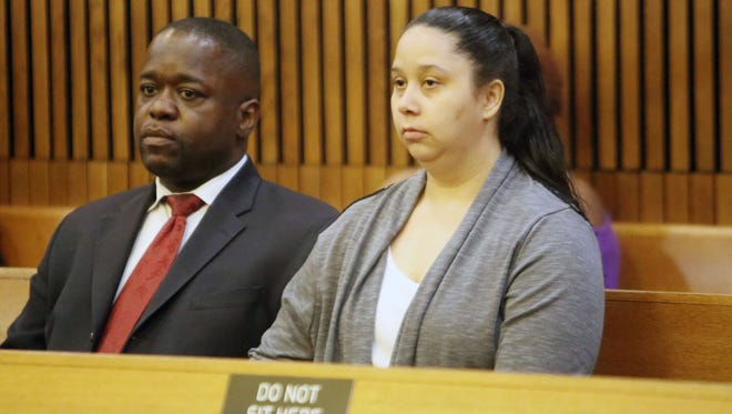 Charlie Bothuell IV waits with his wife Monique Dillard-Bothuell, who is the stepmother of Charlie Bothuell V, for her probation violation hearing Friday, July 11, 2014, at the Wayne County Circuit Court in Detroit.