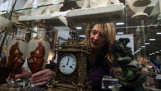 Kathy Romano of Antique Jungle in Lambertville and Lafayette straighten up during the Morristown Armory Antiques Show in 2015.