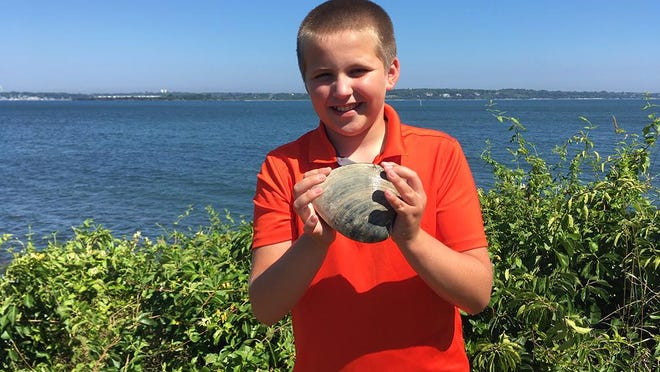 Cooper Monaco of Wakefield shows off the huge quahog he dug up Monday and donated to the University of Rhode Island's Marine Science Research Facility at the Narragansett Bay Campus.