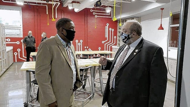 Whitehall-Yearling High School principal Bill Warfield (left) and school board member Leo Knoblauch chat in the school's new Yearling U wing, designed to help students who want careers in business and information technology.