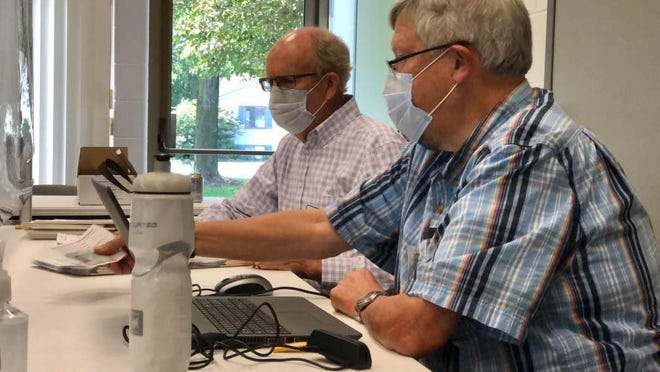 Bob Broene, right, and John Wildeboer help process in-person voters Tuesday, Aug. 4, at Holland Township Fire Station 1 on Riley Street.