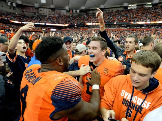 Syracuse quarterback Eric Dungey, center right, and linebacker Zaire Franklin celebrate their win over Clemson after the second half of an NCAA college football game, Friday, Oct. 13, 2017, in Syracuse, N.Y. Syracuse upset Clemson 27-24. (AP Photo/Adrian Kraus)