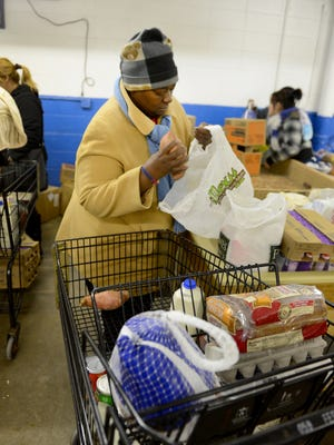 Yvonne Alexander bags up food items she received during distribution at Paul's Pantry in Green Bay.