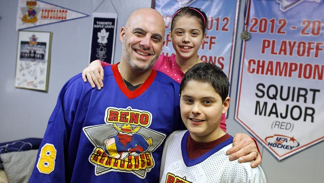 Len Perno, with son Lenny, 12, and daughter Mia, 8, show off Len Perno's old Reno Renegades hockey jerseys in their Chili home this week. Perno, a former Amerks backup goalie, got the jerseys from the Reno team he once played for, after a fan kept them after they were left at the dry cleaners.
