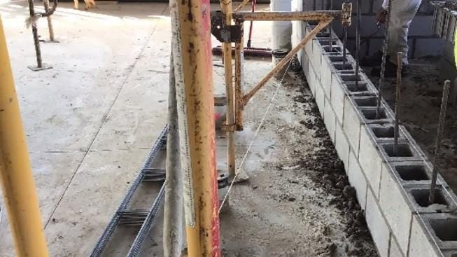 Rebar and cement are being placed in block jail walls to prevent them from being removed.