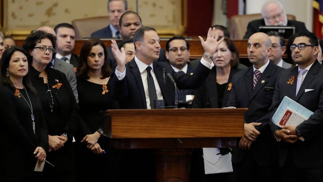 """Texas Rep. Rafael Anchia, D-Dallas, at podium, is surrounded by fellow lawmakers as he speaks against an anti-""""sanctuary cities"""" bill that has already cleared the Texas Senate and seeks to jail sheriffs and other officials who refuse to help enforce federal immigration law, Wednesday, April 26, 2017, in Austin, Texas.   Many sheriffs and police chiefs in heavily Democratic areas warn that it will make their jobs harder if immigrant communities, including crime victims and witnesses,  become afraid of police. (AP Photo/Eric Gay) ORG XMIT: TXEG102"""