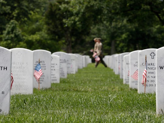 """Soldiers of the 3rd U.S. Infantry Regiment (The Old Guard) place flags at headstones for """"Flags In,"""" at Arlington National Cemetery, on May 25 in Arlington, Va."""