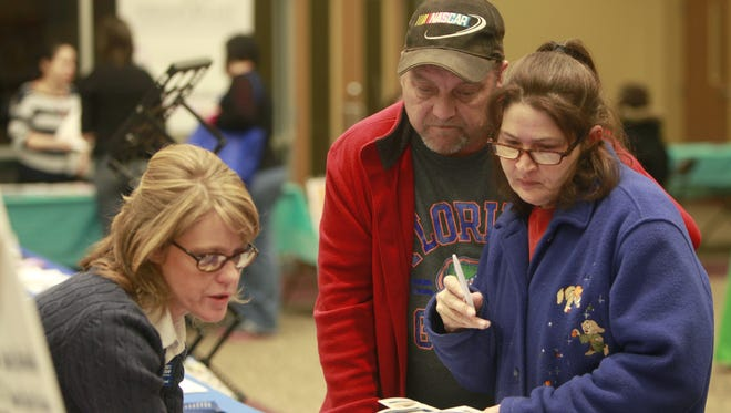 In this file photo, Michelle Garand, director of Affordable Housing and Homeless Prevention at Community Partnership of the Ozarks, helps a couple fill out paperwork during the Life Betterment Fair at Central Assembly in 2014. The fair will be 9 a.m.-3 p.m. Friday.