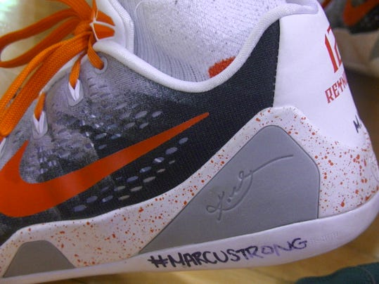 #MARCUSTRONG is written on Jeff Reynolds' left shoe in a show of support to Northeastern classmate Marcus Josey, who was diagnosed a week earlier with a form of leukemia. The school has since rallied around him.