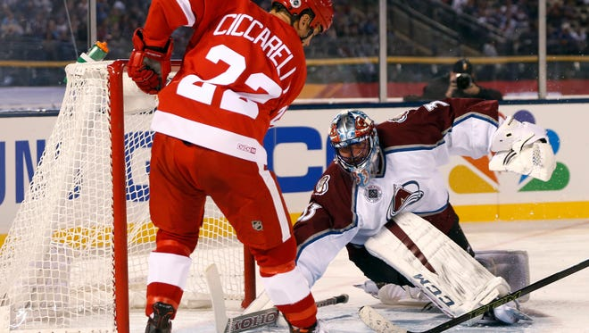 Red Wings right wing Dino Ciccarelli, left, takes a shot against Avalanche goalie Patrick Roy during the second period of the alumni hockey game at Coors Field in Denver on Friday.