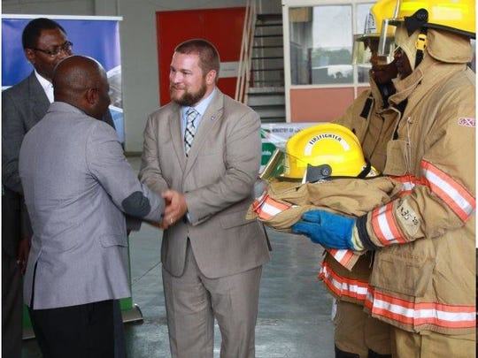Africa Fire Mission founder Dave Moore shakes hands with Vincent Mwale, the permanent secretary of Housing and Local Government for the country of Zambia. AFM delivered fire gear donated by fire departments.