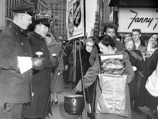 In this 1952 photo,   Rochester officers Thomas Hastings and Leo Balsam, both of traffic bureau look for donations for the Salvation Army at Main and Clinton Streets.