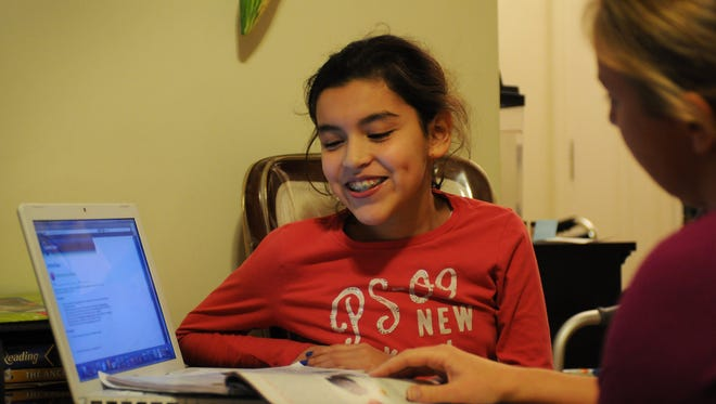 Juliana Valdez (age 11) of Bergenfield, who  lost two toes on her right foot on Aug. 16 when her leg became trapped under a plate at the top of an escalator in Macy's in the Garden State Plaza, studies science with her home school teacher Alison Timme from Bergenfield Roy W Brown Middle School.   Mitsu Yasukawa/ Staff Photographer