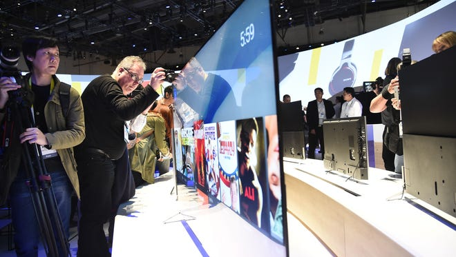 Attendees photograph the Sony Bravia X900C 4K TV, which is only 0.2 inches thick, at the 2015 Consumer Electronics Show in Las Vegas.