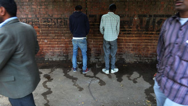 Indian men urinate on a wall at the roadside in New Delhi on Nov. 18, 2014, the eve of World Toilet Day.