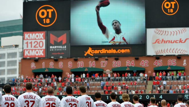 The Cardinals watch a tribute video to memorialize former Cardinal Oscar Taveras before the home opener.