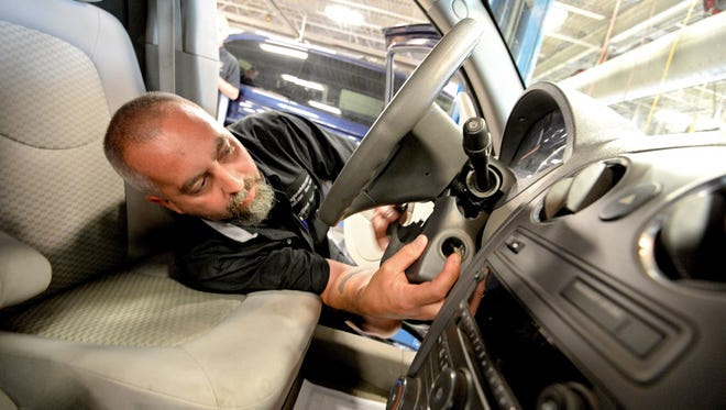Auto technician Billy Morgan works on installing a new ignition switch during a recall repair on a Chevrolet HHR vehicle at Fitzgerald Auto Mallin Frederick, Md., last year