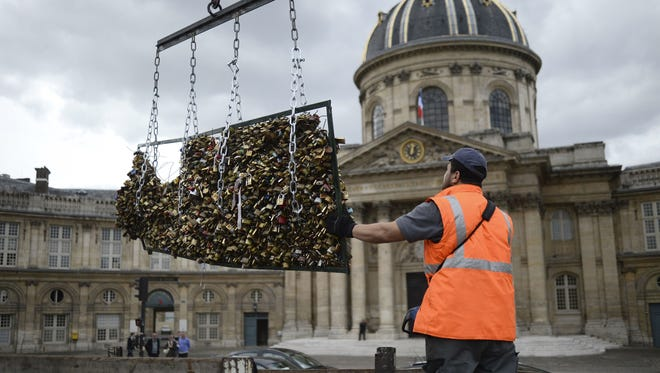"A worker removes ""lock locks"" attached on the railings of the Pont des Arts on June 1, 2015, in Paris."