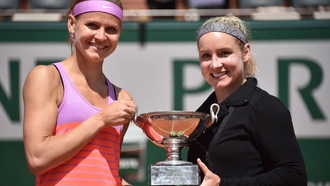 Bethanie Mattek-Sands (R) and Lucie Safarova celebrate with the trophy after winning against Australia's Casey Dellacqua and Kazakhstan's Yaroslava Shvedova during their women's double final match of the Roland Garros 2015 French Tennis Open in Paris on June 7, 2015.