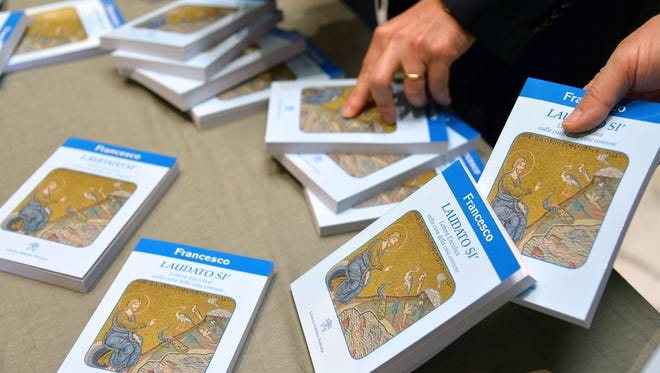 "People hold copies of Pope Francis' encyclical, a collection of principles to guide Catholic teaching, entitled ""Laudato Si"" during its official presentation, on June 18, 2015 at the Sinod hall at the Vatican."