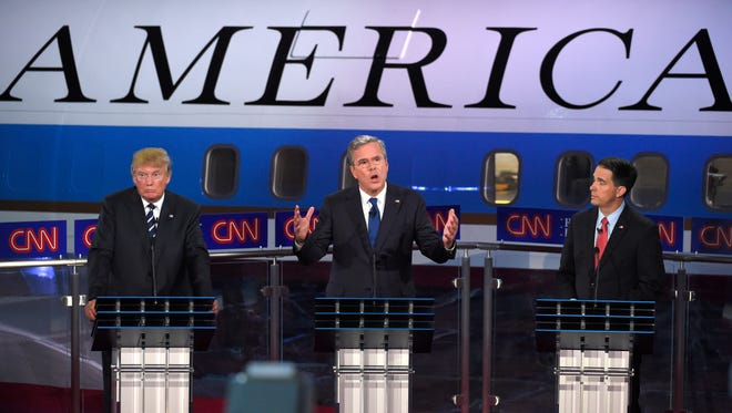 Republican presidential candidate, former Florida Gov. Jeb Bush, center, speaks as Donald Trump, left, and Scott Walker look on during the CNN Republican presidential debate at the Ronald Reagan Presidential Library and Museum.