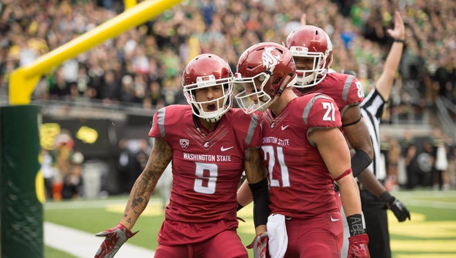 Washington State University Cougars wide receiver Gabe Marks (9) celebrates with teammate River Cracraft (21) after catching a touchdown pass during the first quarter in a game against the University of Oregon at Autzen Stadium.