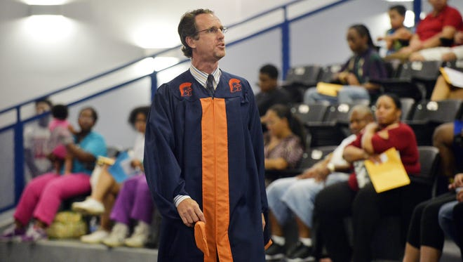 Carolina Academy principal Michael Delaney talks to students about the importance of signing his graduation robe on Monday, August 17, 2015. By signing the robe students are taking an oath to finish school and graduate.