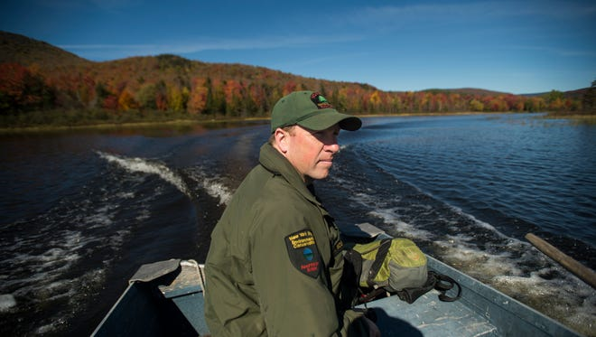 Forest Ranger Jay Scott pilots a metal dinghy on Indian Lake to inspect campsites located on the far side of the lake.