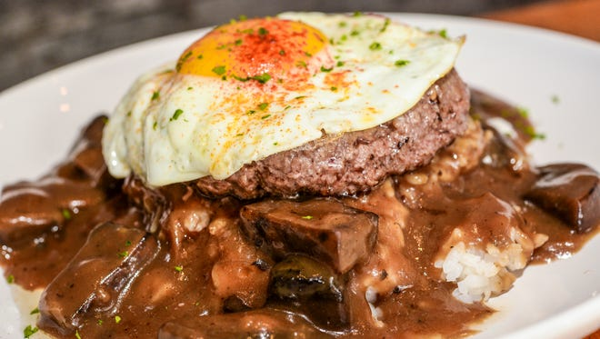 The loco moco, a house specialty consisting of a grilled burger patty on a bed of steamed rice and hearty chucks of Portobello mushrooms, smothered in a caramelized onion gravy, all topped with a fried egg, at the Eat Street Grill in Tumon Nov. 6.