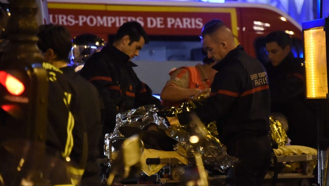 "Firefighters and rescue workers evacuate injured people near the Bataclan concert hall in central Paris, on November 14, 2015. At least 39 people were killed in an ""unprecedented"" series of bombings and shootings across Paris and at the Stade de France stadium on November 13.ORIG FILE ID: 546373104"