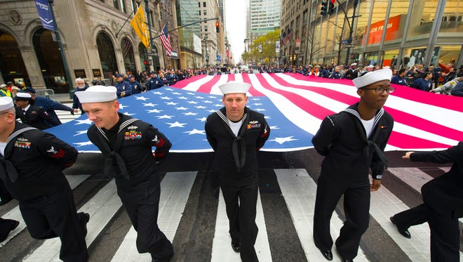 U.S. Navy helps to carry the flag during this year's Veterans Day Parade in New York City. Local events are often sparsely attended.