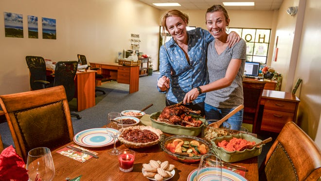 Welcome Home Realty's principal broker/owner Shalyn Allen, left, and office manager Megan Bennett with a Guam-style Thanksgiving meal in Yigo on Friday, Nov. 20.