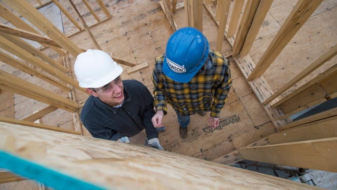 Poudre High School student Sebastian Wells works to install a wall in a home he and his fellow Geometry in Construction classmates are building Friday, November 20, 2015. Students enrolled in the course are building a home with Habitat for Humanity.