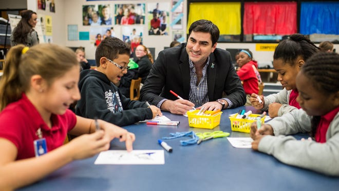 Jacques Rodrigues, son of artist George Rodrigue and executive director of the George Rodrigue Foundation, colors Blue Dog Christmas decorations with students at J. Wallace James Elementary School in Lafayette, La., Wednesday, Dec. 2, 2015.