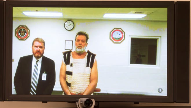 Colorado Springs Planned Parenthood shooting suspect Robert Dear, right, appears via video hearing during his first court appearance, where he was told he faces first degree murder charges, Monday, Nov. 30, 2015, in Colorado Springs, Colo. At left is public defender Dan King.